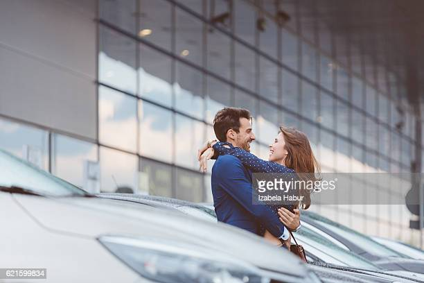 Loving couple embracing at airport car parking