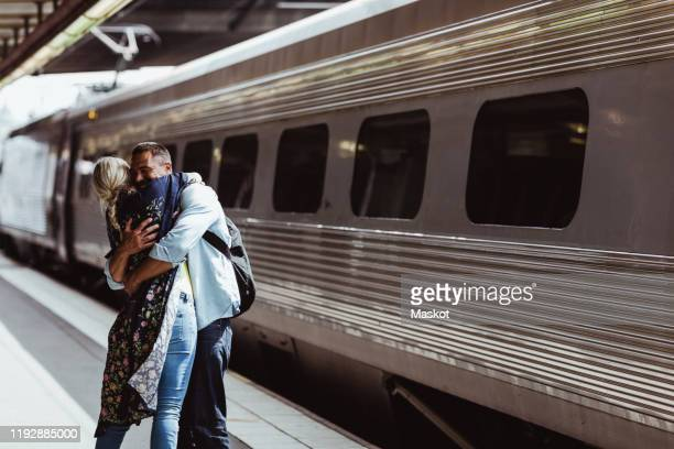 loving couple embracing by train on railroad station platform at station - bahnreisender stock-fotos und bilder