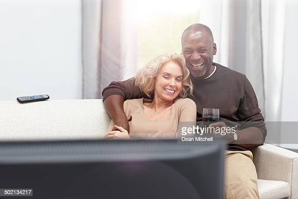 Loving couple enjoying watching TV with a glass of wine