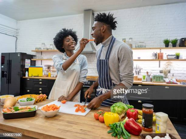 loving couple feeding each other while cooking dinner at home - apron stock pictures, royalty-free photos & images
