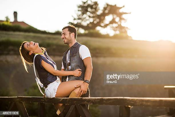 Loving couple flirting on a bridge and laughing.