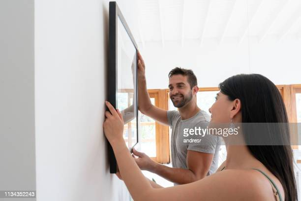 loving couple hanging a picture together at home - hanging stock pictures, royalty-free photos & images