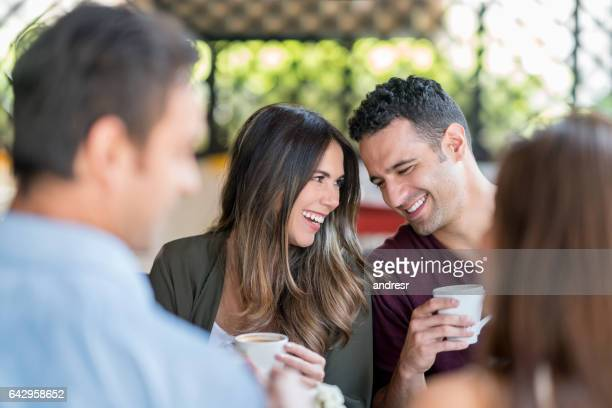 Loving couple having a cup of coffee with friends