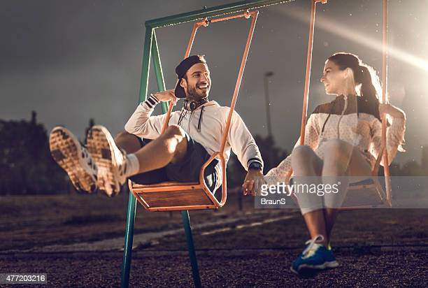 Loving couple having fun while swinging on a playground.