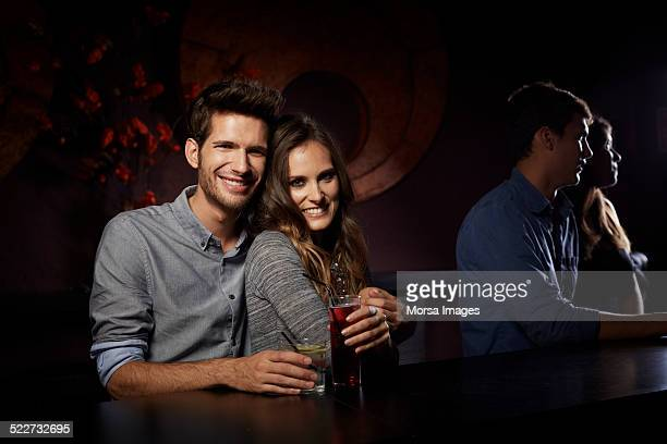 Loving couple holding drinks at table in nightclub
