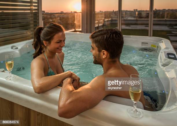 Loving couple holding hands and talking while enjoying in hot tub.