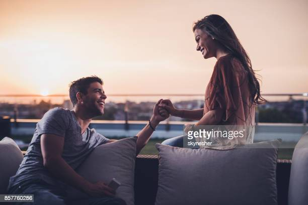 Loving couple holding hands while talking on a balcony at sunrise.