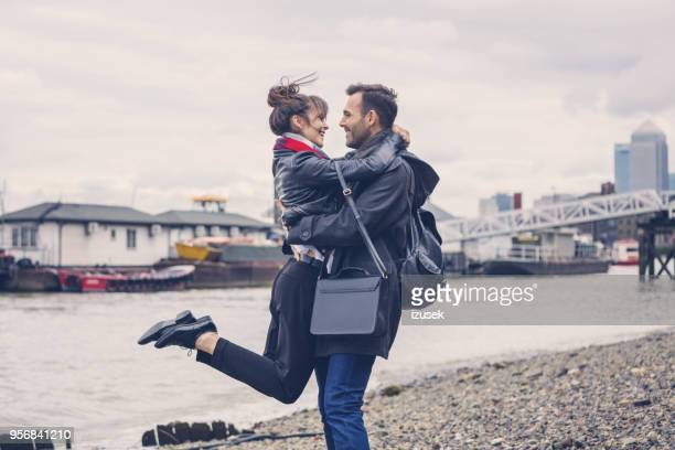 verliefde paar knuffelen op de oever, stad op de achtergrond - gezicht aan gezicht stockfoto's en -beelden