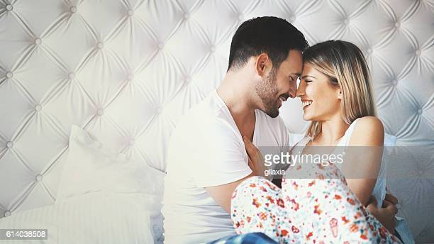 loving couple in bed. - couple and kiss and bedroom stock photos and pictures