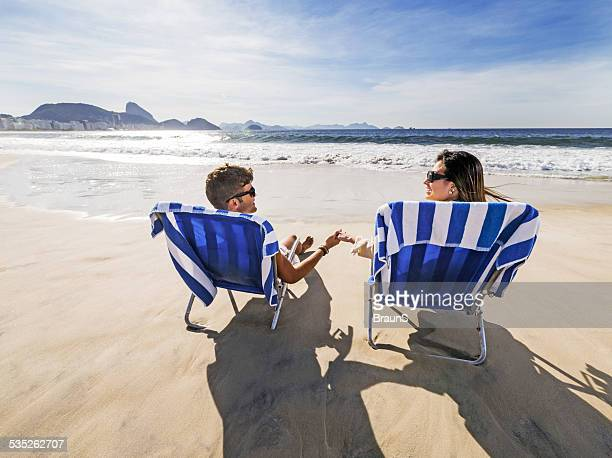 Loving couple in deck chairs on the beach.