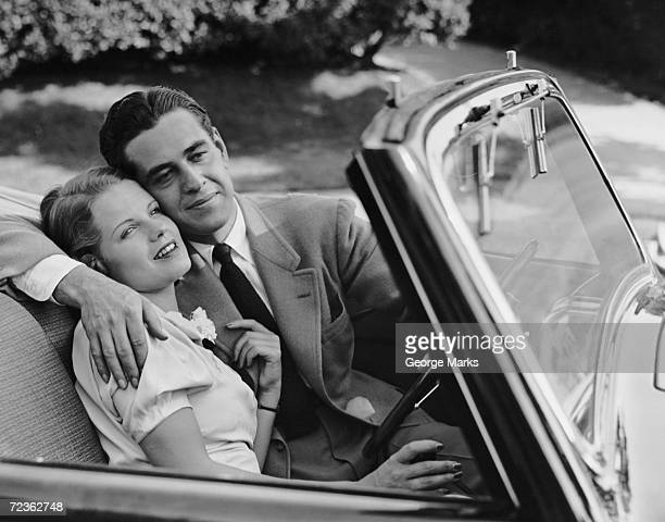 1950s: Loving couple in sports convertible.