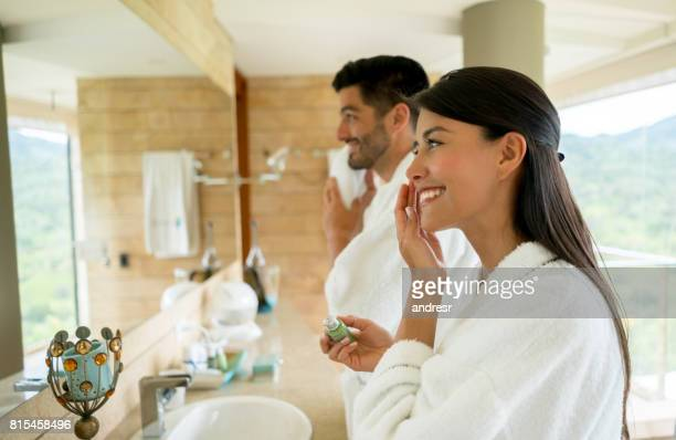 loving couple in the bathroom getting ready in the morning - grooming product stock photos and pictures