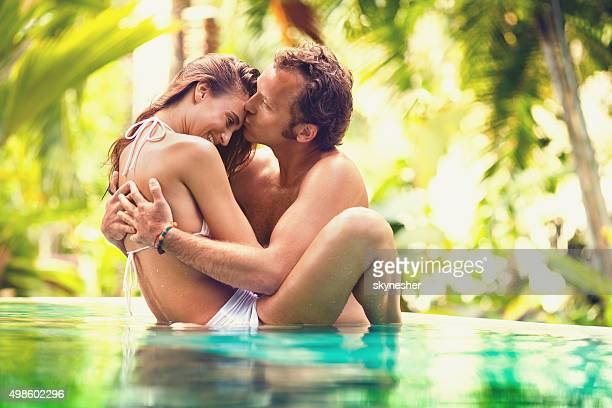 Loving couple kissing in tropical pool during summer.