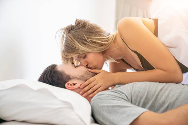 loving couple kissing on the bed.happy couple lying together in the bed