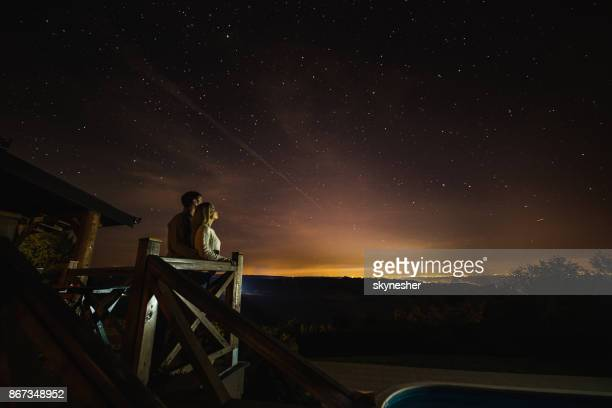 Loving couple looking at breathtaking view of constellation from their balcony.