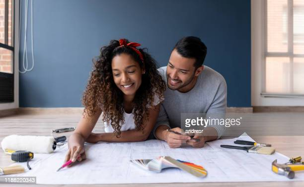 loving couple looking at the blueprints of their new house - renovation stock pictures, royalty-free photos & images
