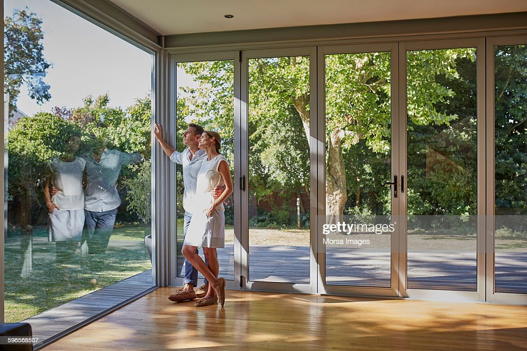 Loving couple looking through glass window : Stock-Foto