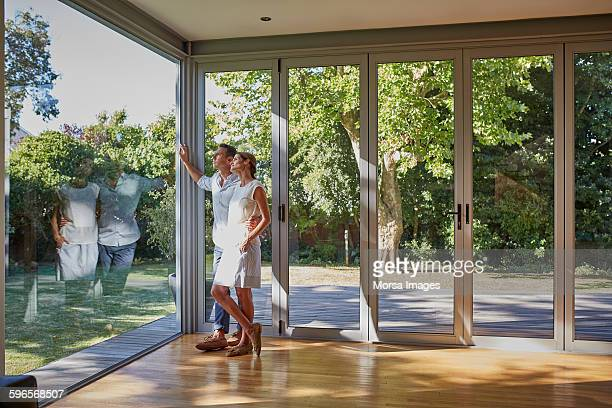 loving couple looking through glass window - hommes nus photos et images de collection