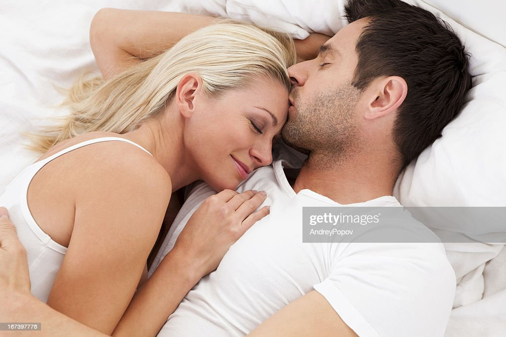 Loving couple lying in bed : Stock Photo