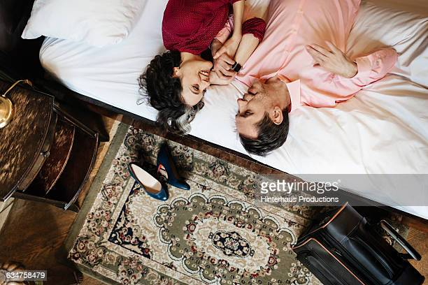 loving couple lying in hotel bed together - ungestellt stock-fotos und bilder