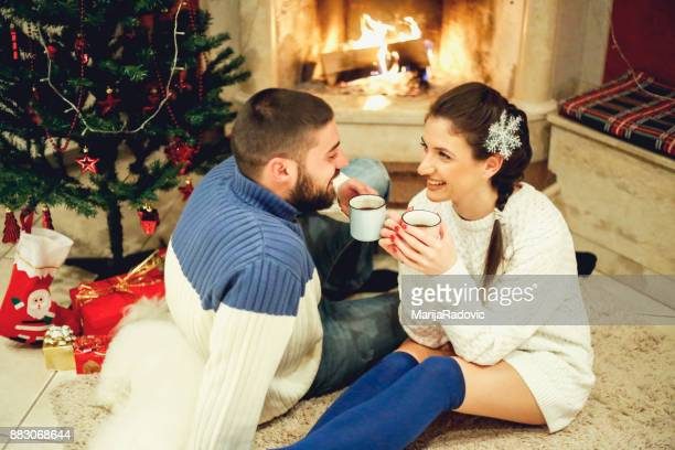 Loving couple near fireplace in Christmas decorated house interior