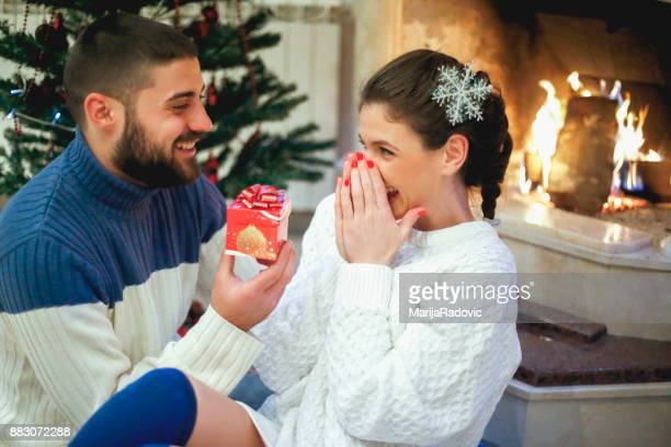 Loving couple near fireplace in Christmas decorated house interior.Girlfriend recived Christmas gift from his boyfriend