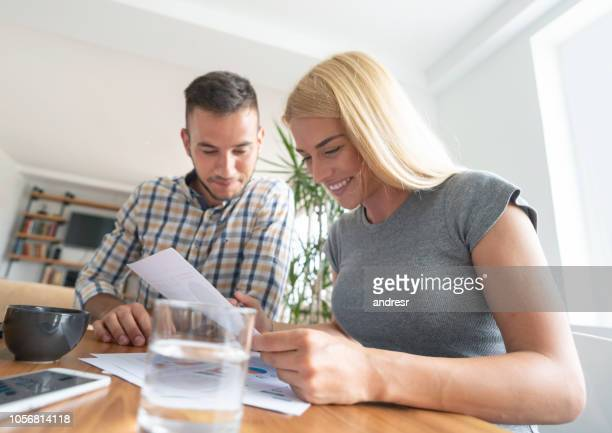 Loving couple paying bills at home