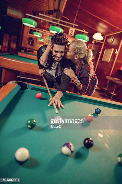 Loving couple playing billiard in a pool hall.