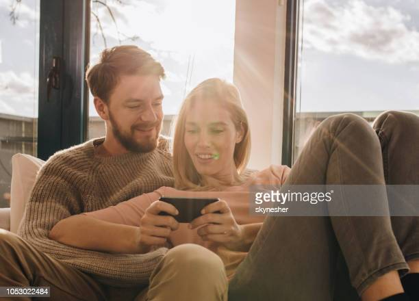 Loving couple relaxing at home and using cell phone.