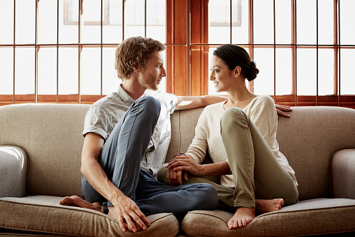 Loving couple siting on sofa at home - gettyimageskorea