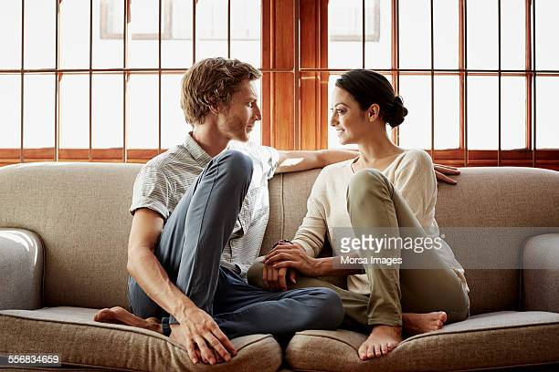 loving couple siting on sofa at home - face to face stock pictures, royalty-free photos & images
