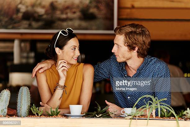 loving couple sitting at cafe - senza maniche foto e immagini stock