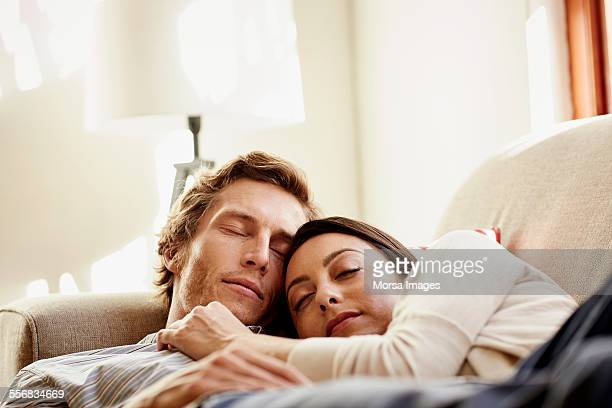 Loving couple sleeping on sofa