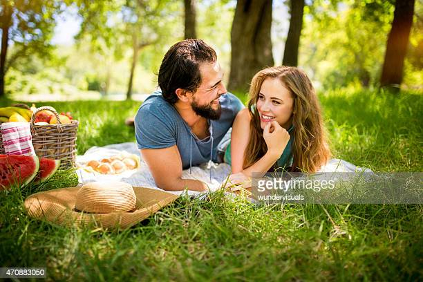 Loving couple smiling at each other on a picnic blanket