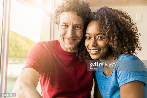 Loving couple smiling by window at home
