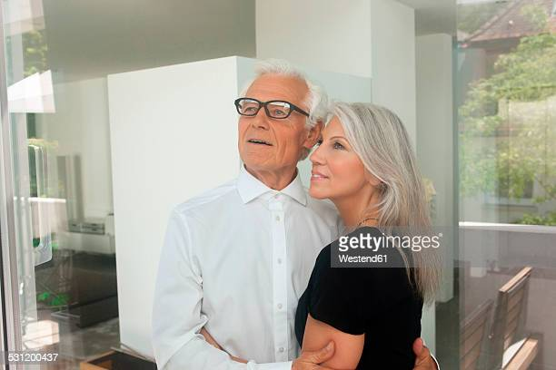 Loving couple standing together looking out of the window