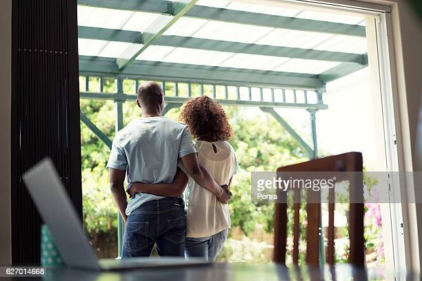 Loving couple standing with arms around at home
