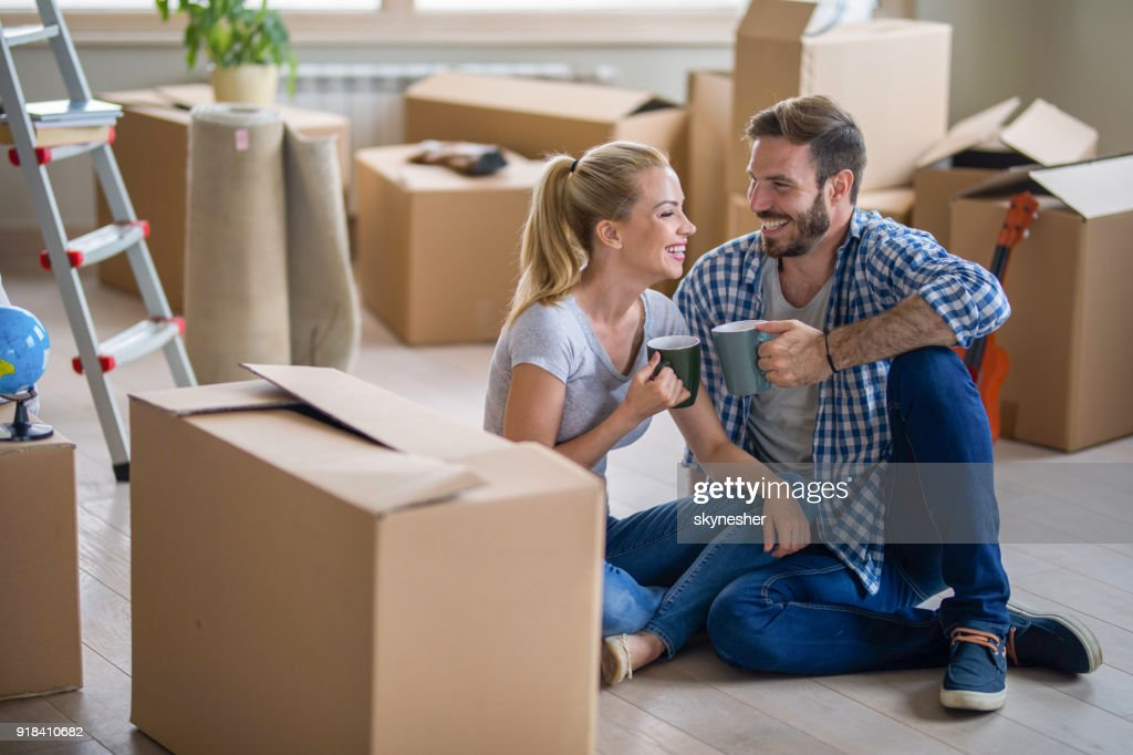 Loving couple talking while resting from relocating into a new apartment. : Stock Photo