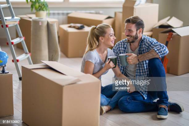 loving couple talking while resting from relocating into a new apartment. - unpacking stock pictures, royalty-free photos & images