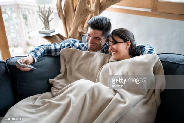 couple d'amoureux de regarder la télévision dans un chalet d'hiver - hot couple photos et images de collection