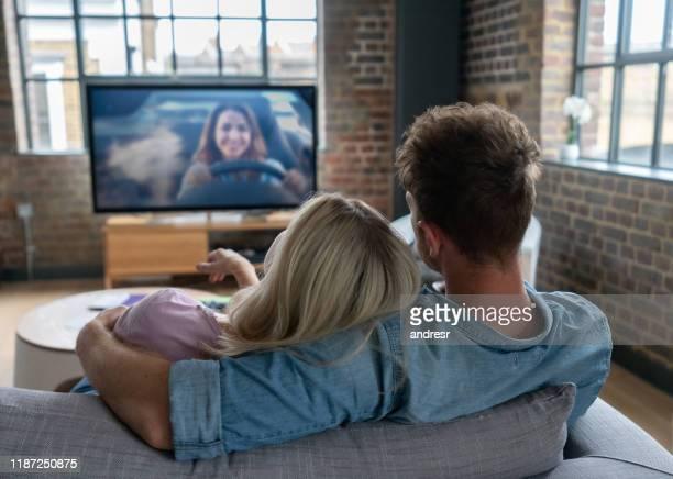 liefdevolle paar kijken naar televisie thuis - televisie kijken stockfoto's en -beelden