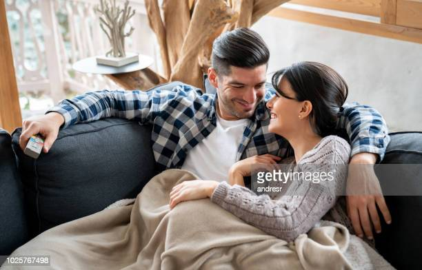 loving couple watching tv in their winter lodge while lying on the sofa - heat stock pictures, royalty-free photos & images