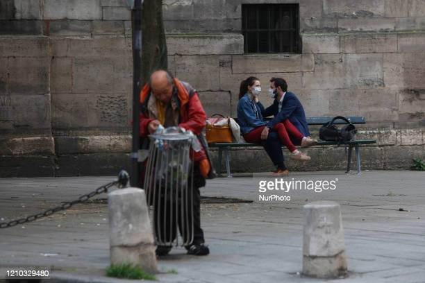 A loving couple with a protective mask hug on a bench in front of the Saint Sulpise church in Paris on April 17 during the lockdown in France to...