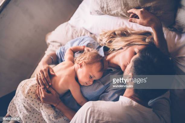 loving couple with sleeping baby kissing in bed - coppia a letto foto e immagini stock