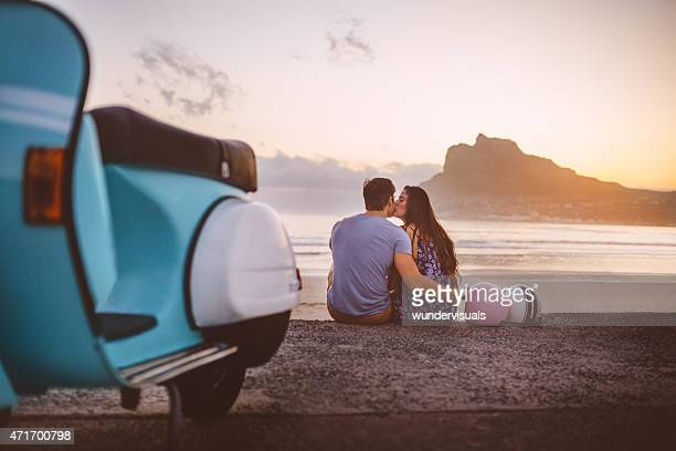 Loving couple with their scooter kissing at the beach
