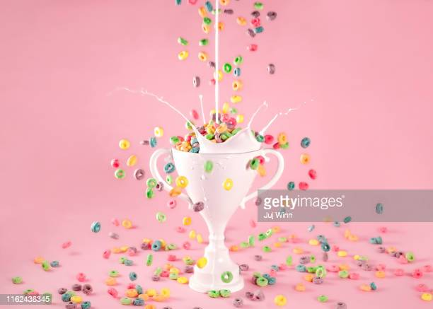 loving cup trophy with breakfast cereal and milk splash - award stock pictures, royalty-free photos & images