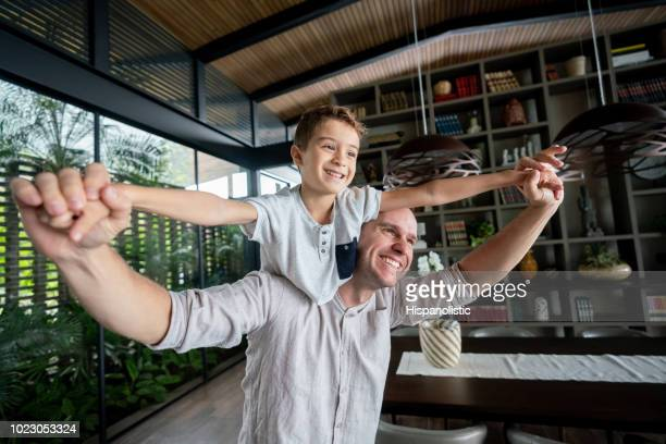 Loving dad carrying his son on shoulder having fun at home