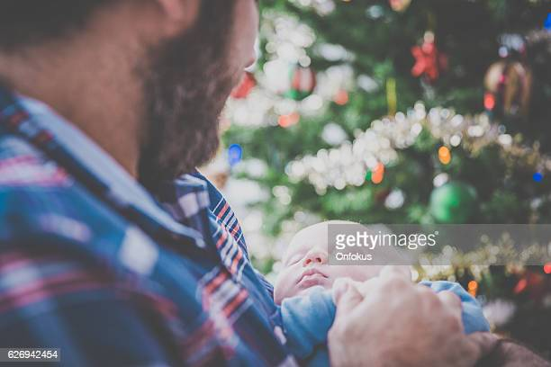 Loving Dad With Newborn Baby Close to Christmas Tree