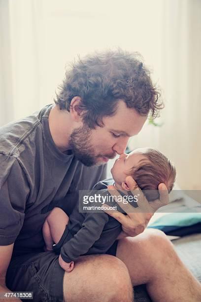 Amorevole padre con il neonato sul divano nel soggiorno separato.