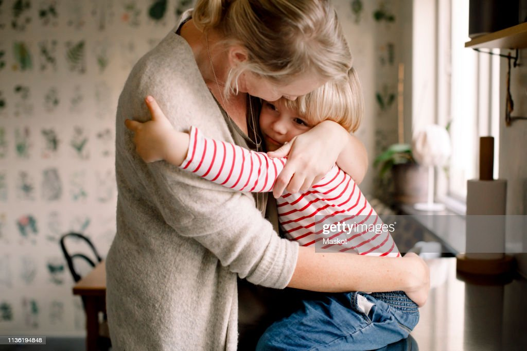 Loving daughter embracing mother while sitting on kitchen counter at home : Stock Photo